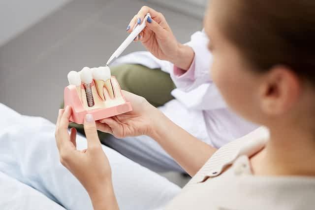 Dentista explicando para paciente dúvidas sobre implante dentário de carga imediata