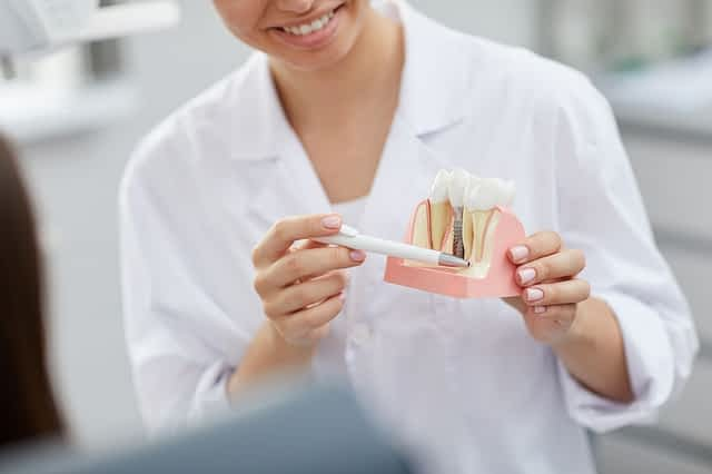 Dentista explicando a importância da osseointegração nos implantes de carga imediata